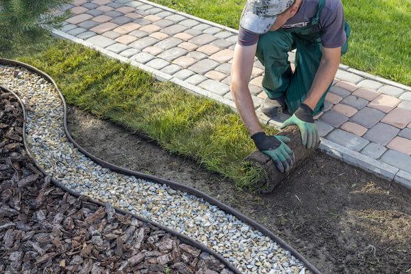Dieses Bild zeigt einen Arbeiter bei der Verlegung von Rollrasen und dient der Verdeutlichung des Themas 'Entsorgungsservice für den Garten und Landschaftsbau in Berlin'.