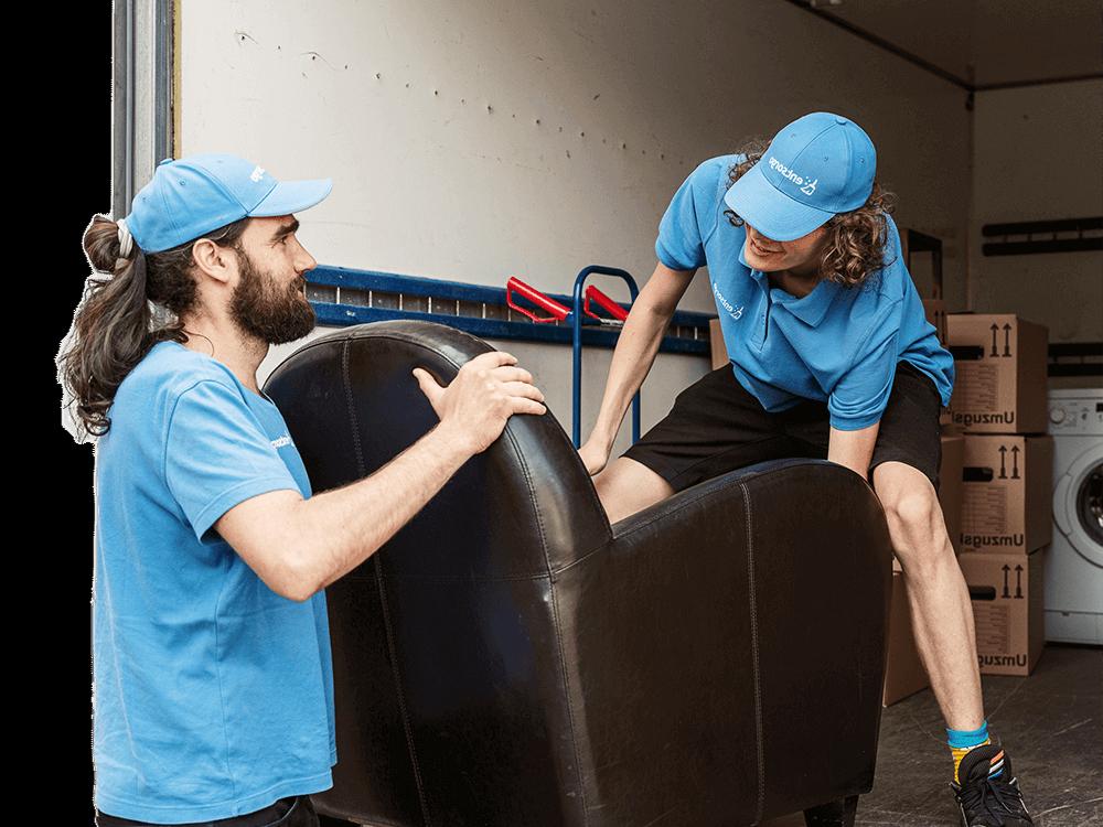 Dieses Bild zeigt 2 entsorgo Mitarbeiter bei einer Wohnungsauflösung, während sie einen Sessel in den LWK laden.